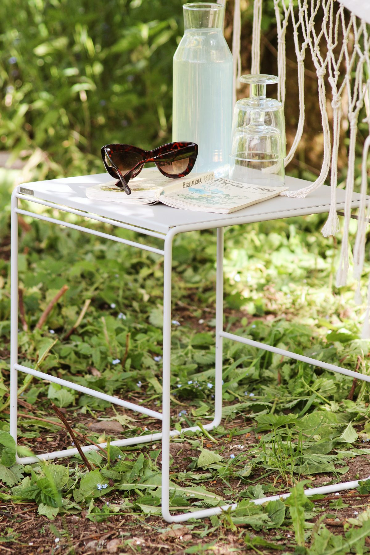 Utemöbel, karaff, solglasögon och bok